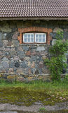 Wall from granite stones with a window and a tree, the old aspha Stock Photo