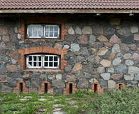 Wall from granite stones with a windows and  the old asphalt roa Stock Photos