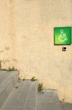 Wall with a green sign. Yellow concrete wall with grey stairs of the asphalt Royalty Free Stock Photos