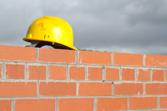Wall and helmet. A yellow safety helmet on the top of a red brick wall with pointing Stock Image