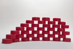 Wall with holes pattern. made of red ribbed plastic bottle caps, stacked in rows. Shallow depth of field. focus at the front elem. Ent of footing stock photography