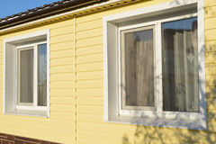 wall of the house coated with yellow siding Royalty Free Stock Image