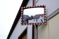 Traffic mirror with house reflections. On the wall of a house at a confusing junction hangs a traffic mirror royalty free stock image