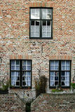 Wall of house from red brick with three windows Stock Photography