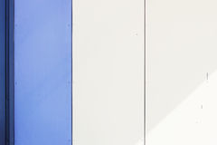 The wall of the house, trimmed with colorful panels, painted in bright colors. Blue and beige Royalty Free Stock Image