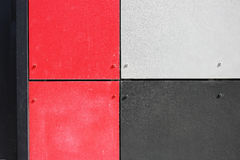 The wall of the house, trimmed with colorful panels, painted in bright colors. Grey, black and red.  royalty free stock images