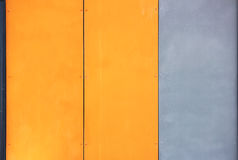 The wall of the house, trimmed with colorful panels, painted in bright colors. Grey and orange. Stock Images
