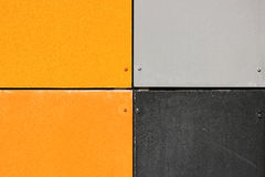 The wall of the house, trimmed with colorful panels, painted in bright colors. Grey and orange Stock Photos