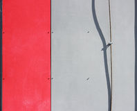 The wall of the house, trimmed with colorful panels, painted in bright colors. Red and grey. The wall of the house, trimmed with colorful panels, painted in stock photo