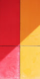 The wall of the house, trimmed with colorful panels, painted in bright colors. Red and orange. The wall of the house, trimmed with colorful panels, painted in royalty free stock photography