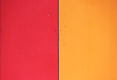 The wall of the house, trimmed with colorful panels, painted in bright colors. Red and orange. The wall of the house, trimmed with colorful panels, painted in stock photography