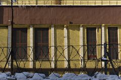 Wall of an industrial building behind a fence with barbed wire stock image