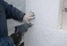 Wall Insulation. Builder drilling wall for installing anchors to hold rigid insulation foam board. Attach rigid foam insulation to a concrete wall royalty free stock photos