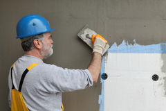 Wall insulation, spreading mortar over mesh and styrofoam. Worker spreading mortar over styrofoam insulation and mesh with trowel stock photography