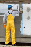 Wall insulation, spreading mortar over mesh and styrofoam. Worker spreading mortar over styrofoam insulation and mesh with trowel stock images