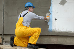 Wall insulation, spreading mortar over mesh and styrofoam Stock Photography