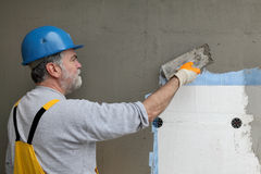Wall insulation, spreading mortar over mesh and styrofoam Royalty Free Stock Image