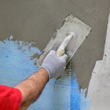 Wall insulation, spreading mortar over mesh stock photography