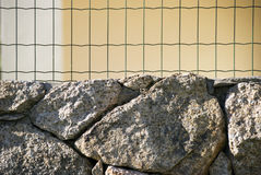Wall and iron fence. Close-up of a wall with metallic wire net or chain link stock photography
