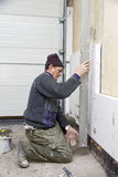 Wall isolating. A worker kneeling at a wall, putting on wall isolation, checking if the wall is even Royalty Free Stock Photo