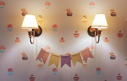 Wall lamp in the children`s room. Chandelier in the children`s room. Close-up. Flags between the lamp. Cake Wallpapers stock photography