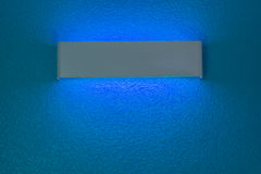 Wall lamp with light shade. Modern wall lamp with light shade on blue cement wall royalty free stock photography