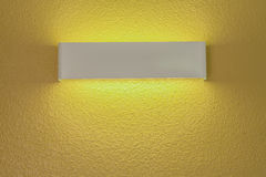 Wall lamp with light shade. Modern wall lamp with light shade on gold cement wall stock photos