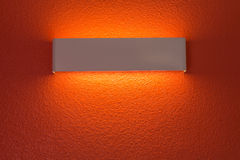 Wall lamp with light shade. Modern wall lamp with light shade on orangered cement wall stock image
