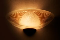 Wall lamp litWall lamp lit. A warm glow with warm yellow walls of its own Royalty Free Stock Image