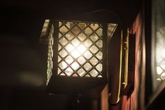 Wall lamp shines in the dark. Wall lamp with yellow shade from canvas royalty free stock photography