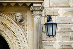 Wall lantern. Entrance door with a trimmed stone fresco the man a wall lantern Stock Images