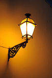 Wall lantern lit up at night. Lantern on a wall in the Plaza de Santa Maria at night, Antequera, Malaga Province, Andalucia, Spain, Western Europe Stock Image