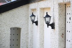 Wall lanterns on old house, perspective view. Perspective view of two wall lanterns on old house, taken in Mother Shipton's Park, Knaresborough, North Yorkshire Stock Images