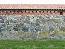 Wall from large granite stones with tile roof and grass as backg Stock Photos