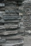 Wall of layered stones in a rough hewn pattern with wall in background showing depth and extent of the wall. Wall of layered stones in a rough texture of hewn stock image
