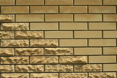 Wall of light smooth and uneven bricks. Laying of light smooth and uneven brick in the wall of the house stock image
