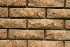 Wall of light uneven brick. Laying of light uneven brick in the wall of the house royalty free stock photography