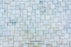 Wall lined with small bright ceramic or marble tiles, texture royalty free stock images