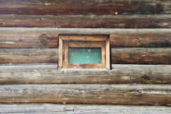 Wall of a log cabin with a small window Royalty Free Stock Images