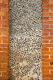 Wall made of brick and concrete with little stones Stock Photography