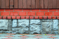 Wall made of different materials. The foundation of the fence. Elements of multimaterial fence, wood planks, brick walls and stone base Royalty Free Stock Image