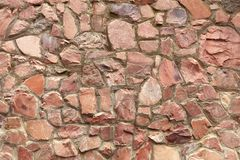 The wall is made of natural raw coarse red granite. The wall is made of natural coarse red granite with embroidered borders of cement royalty free stock image