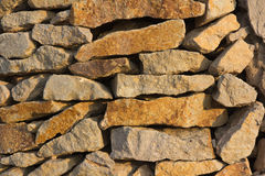 Wall made of natural stone in the evening sun Royalty Free Stock Photo