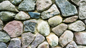 Wall made of natural stones. Background Stock Image