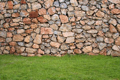 Wall made with natural stones and grass in front. As background Stock Photos