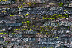 Wall made of natural stones with the growing moss Stock Photo