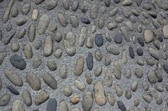 The wall is made of oval cobblestones of different sizes.Texture or background. The wall is lined with stones oval shape.Texture or background royalty free stock image
