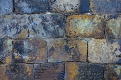 A wall made of rough stone. Ancient brickwork. Bricks are hewn out of untreated stone. Rough, textured surface. On the stones are black traces of fire. An old Stock Photos