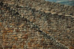 Wall made of rough stones rising along the hill in Marvao. Close-up of large solid wall made of rough stones, rising along the hill in a sunny day at Marvao. An royalty free stock images