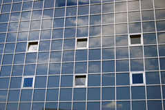 A wall made of square glass bricks. Blue sky with clouds reflection. Stock Photos